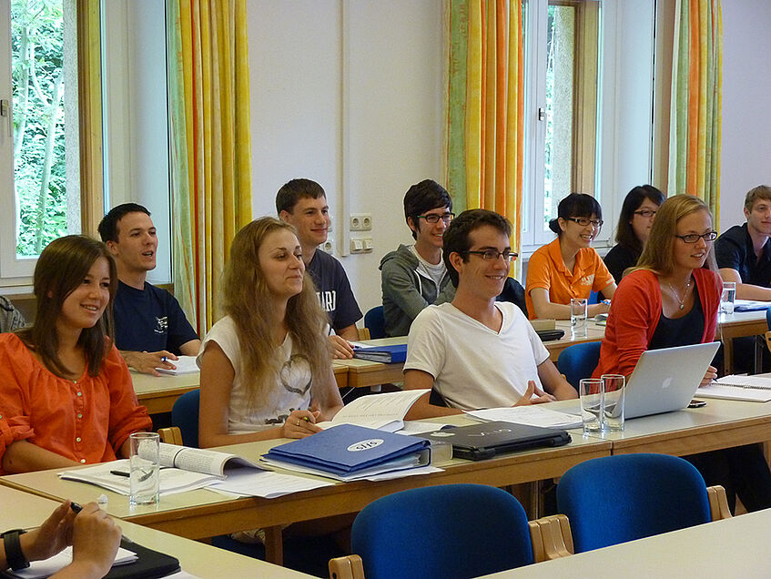 A group of students sitting in class, looking towards the front, and smiling.
