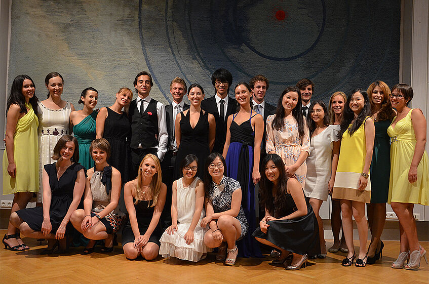 A group of students dressed up in cocktail dresses and suits.