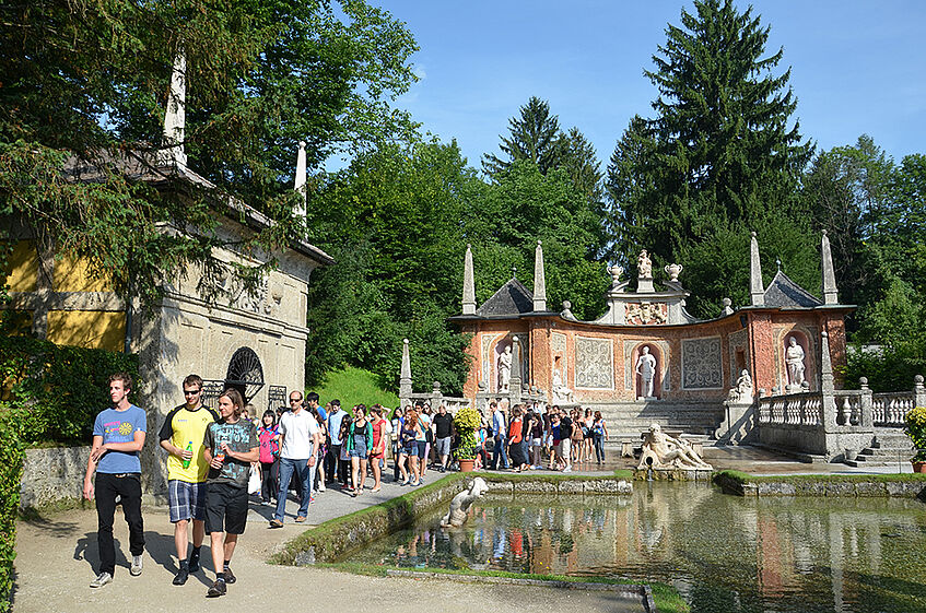 Students taking a guided tour of the trick fountains in Schloss Hellbrunn.