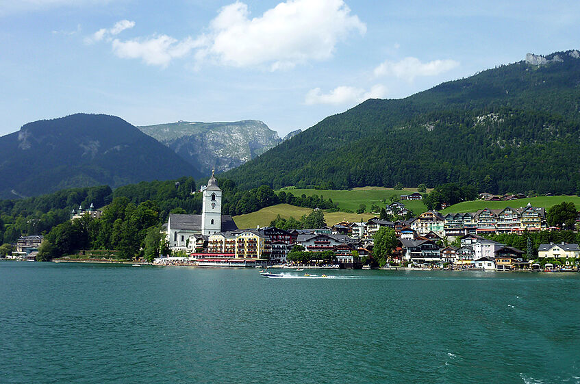 The village St. Wolfgang seen from the lake, with water in the foreground and a mountain range in the background.