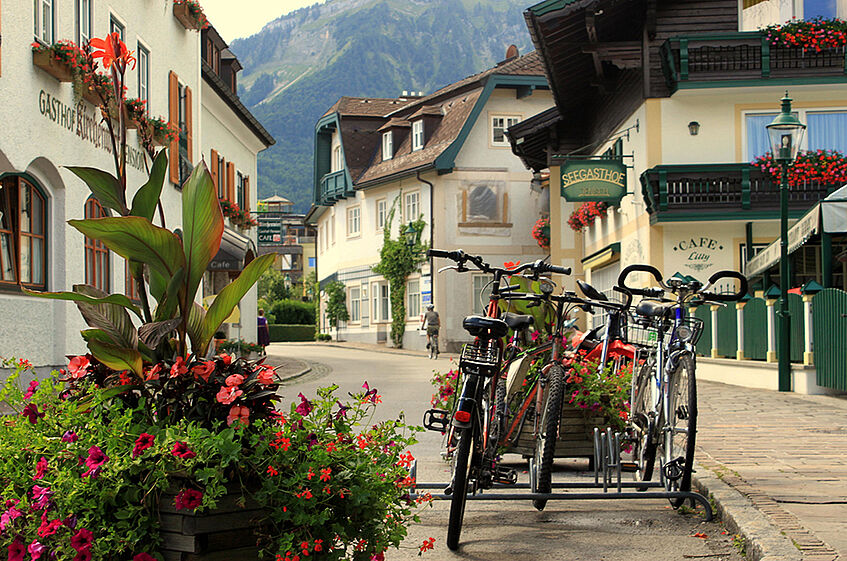 Village street with quaint houses with balconies and a flower arangement and three bycicles in the foreground.