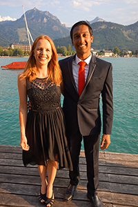 Couple in elegant clothes on wooden pier with lake in the background